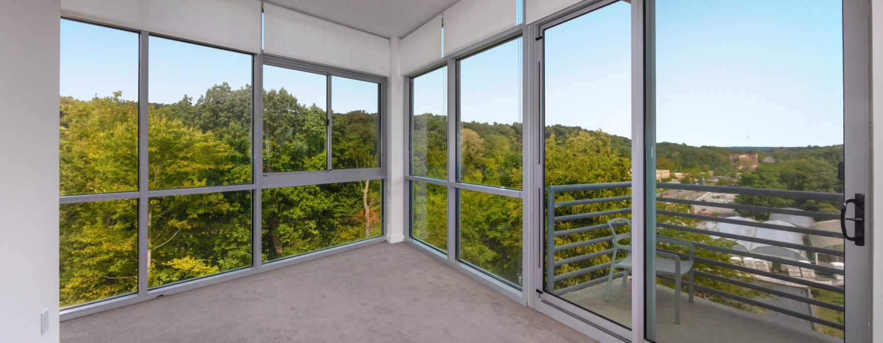 huge panel windows surround living room providing beautiful woodland views