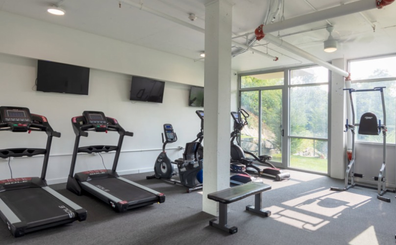 open fitness center with overhead lighting throughout